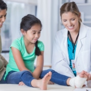 Female doctor wraps young girl's injured ankle