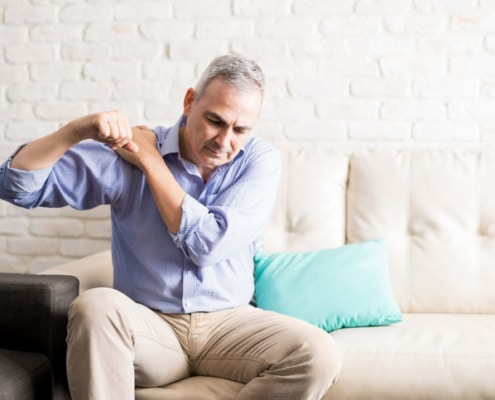 Mature man with shoulder pain at home